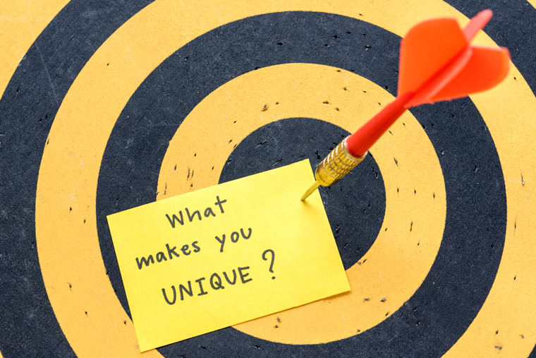 "Finding ideas for a blog name by using brand based names. A dartboard with sticky note pinned to it saying: ""What makes you unique"""