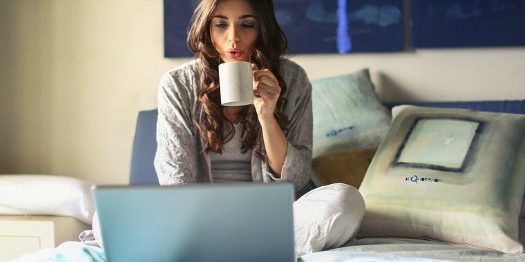 Woman sitting on a bed with a cup of coffee and looking at the laptop. It's just a synonym of how to make money with a blog by becoming a freelancer.